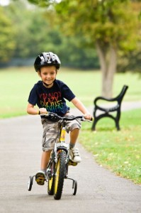Young boy riding his kids bike with stabilisers in the park.